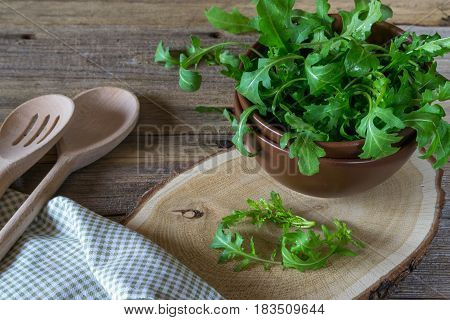 Fresh garden organic arugula, ruccola  in bowl  on rustic background ready for salad. Vintage still life