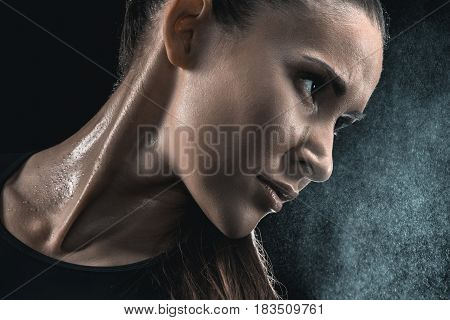 Close-up Portrait Of Young Sweaty Fitness Woman Looking Away On Black