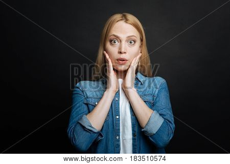 With puzzled emotions inside . Emotional young frustrated woman demonstrating confused emotions and raising hand to the head while standing against black background