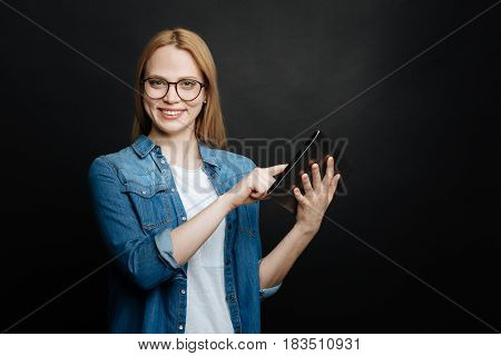 Explore technologies with me . Happy amused young woman expressing positivity and smiling while using tablet and standing in the studio