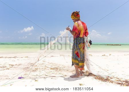Traditional african local rural fishing on Paje beach, Zanzibar, Tanzania. Traditionally dressed local woman pulling fishing net, catching small fish.