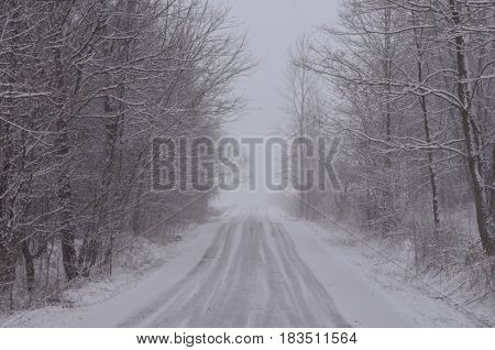 Snow covered Country road on snowy winter day