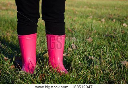 Child wearing pink rain boots on the grass