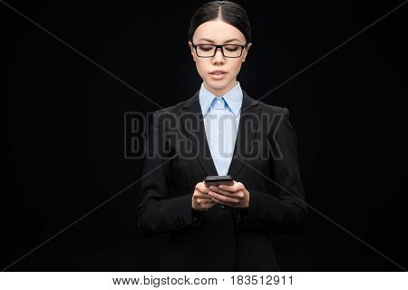 Brunette Businesswoman In Black Suit Using Smartphone Isolated On Black