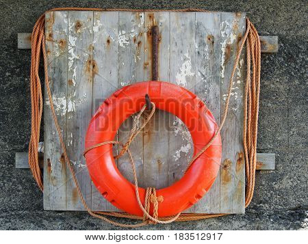 life buoy on a weathered wooden board with faded orange rope harbour