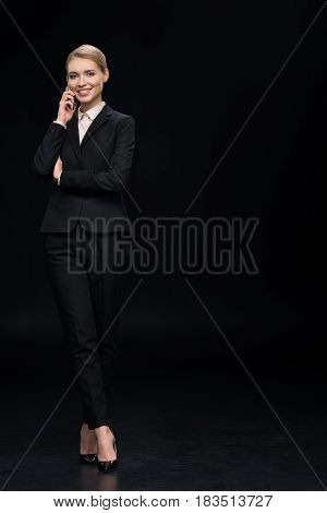 Smiling Businesswoman Talking On Smartphone Isolated On Black