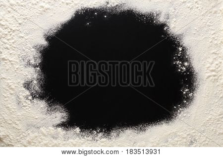Abstract background. Sprinkled wheat flour frame on black. Top view on blackboard. Baking concept, cooking dough or pastry.