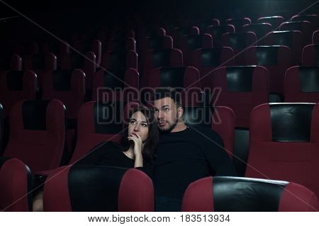 Happy romantic couple watching movie in empty theater. Young smiling adults having fun together, Man hugging girlfriend. Cinema, entertainment and leisure concept.