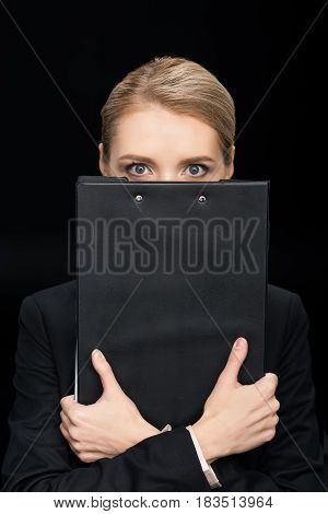 Businesswoman Obscuring Face With Notepad Isolated On Black