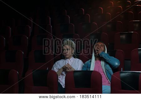 Young romantic couple in cinema theater. Blonde girl watching movie while her boyfriend yawning. Cinema, entertainment and leisure concept.