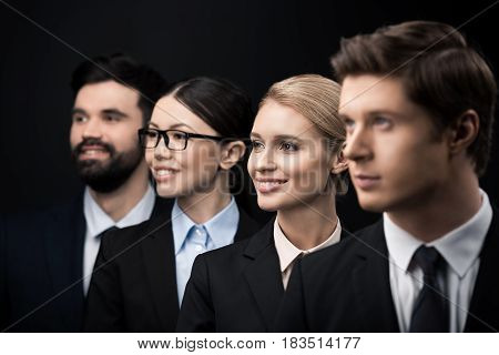 Side View Of Business People Standing In Row Isolated On Black