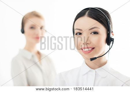 Smiling Call Center Operator In Headset With Colleague Behind Isolated On White