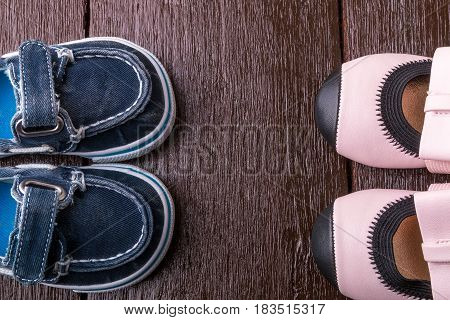 Baby Boy And Girl Shoes On Wooden Background. Child Footwear. Top View.