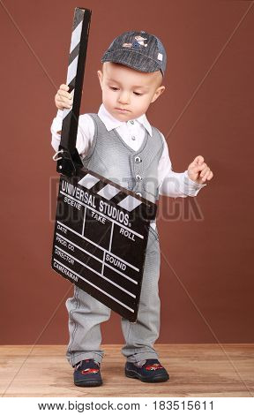 Cute little boy with cinema clapper. In a denim suit. On a brown background