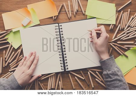 Close-up of creative designer drawing something in sketchbook at workplace. Top view flat lay shot of many blank sticky notes, color pencils on wooden table background, copy space, nobody, objects