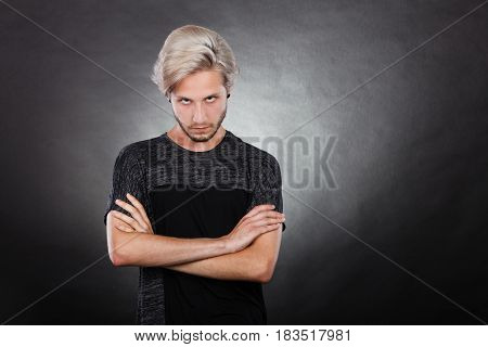 Negative emotion feelings attitude. Angry grumpy young man looking very displeased standing with arms folded serious face expression on dark