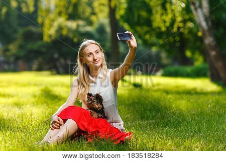 Young beautiful woman taking selfie with her dog - small Yorkshire terrier. Summer park.