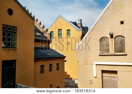 Traditional Norwegian houses painted in yellow with with tile roofs