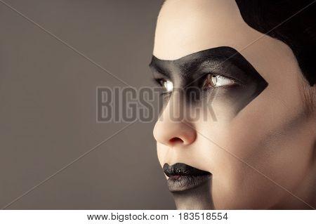 attractive woman with creative dark makeup closeup