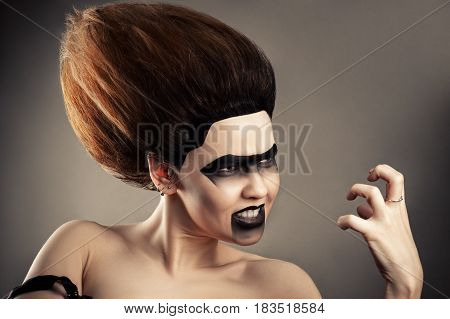 angry brunette woman with dark makeup and lush hairdo