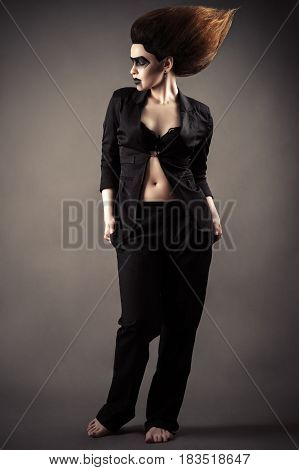 fashionable woman with dark makeup in business suit standing full length