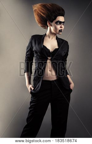 fashionable woman with dark makeup in business suit