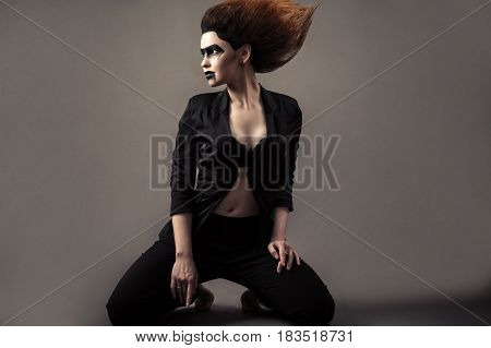 beautiful woman kneeling with lush hair and dark makeup