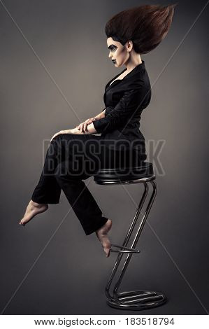 fashionable beautiful business woman sitting on bar stool with lush hair and dark makeup