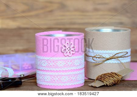 Pens and scissors holders. Creative recycled tin cans for storage of stationery. Decoration tin cans using a felt, lace and button. Scissors, felt sheets, organizer and lace on a wooden table. Closeup