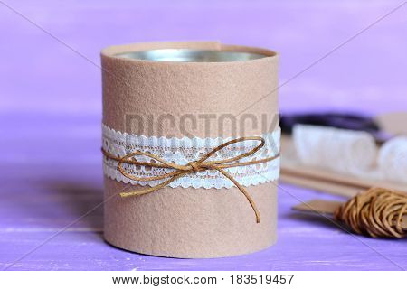 Pencils and scissors decorative holder. Recycled tin can for storage of stationery on wooden background. Tin can decorated with felt and lace. Simple and quick home crafts idea. Closeup