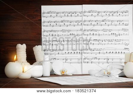 Composition of music sheets and spa supplies on table