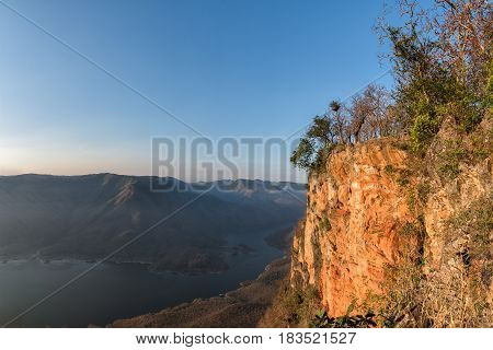 Giant red rock cliff mountian above the lake. Mae Ping National Park Thailand.