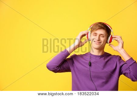 Handsome young man listening to music on color background