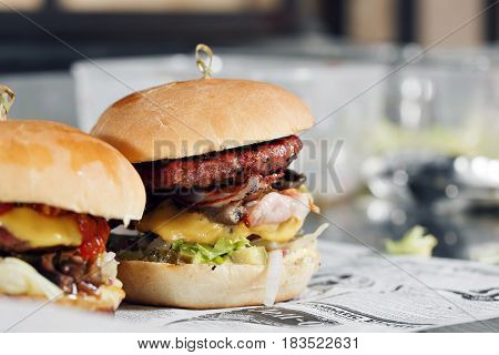 Delicious burgers with beef, tomato, cheese and lettuce. cooked on the grill assembled