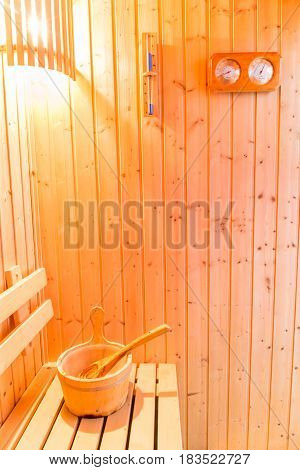 Sauna accessories in sauna room wooden bucket place on bench and bath thermometer and timer on wooden wall.