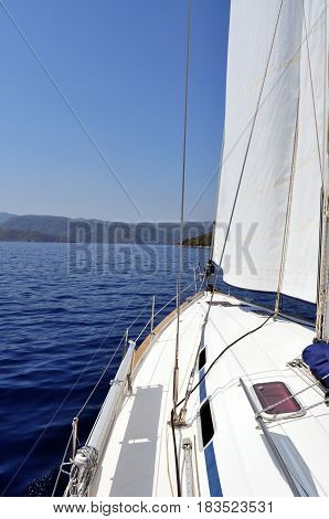 Ultramarine blue water and land viewed from deck of yacht: The blue waters of the turquoise coast in Turkey and land as viewed from the deck of a sailing yacht.
