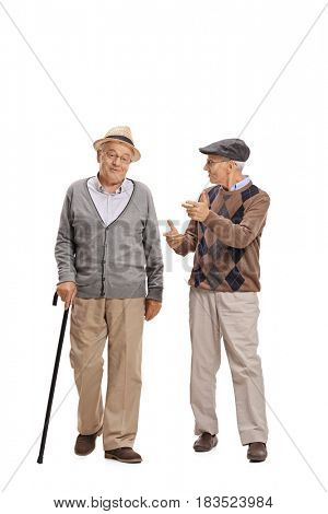 Full length portrait of two elderly men walking towards the camera and talking to each other isolated on white background