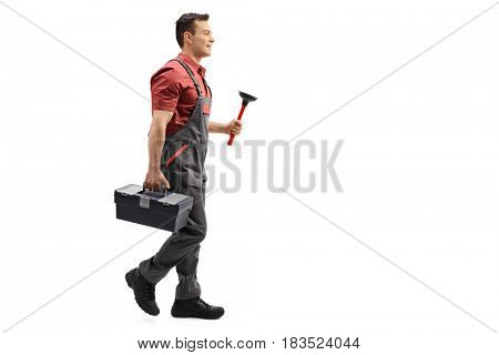 Full length profile shot of a plumber holding a plunger and a toolbox walking isolated on white background