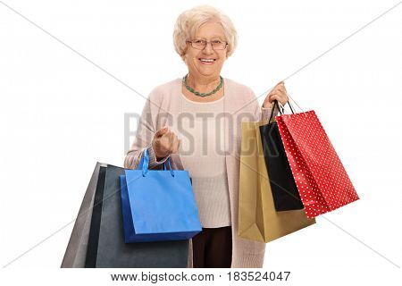 Happy mature woman with shopping bags isolated on white background