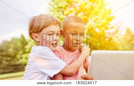 Boys with laptop learning about technology in the park in summer