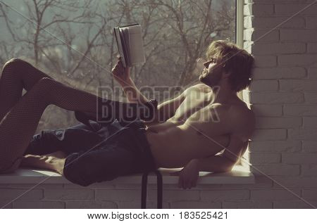 Muscular man or macho with fit naked torso and female legs in erotic black fishnet tights and shoes with high heels on window sill on blurred natural background. Reading book and relax