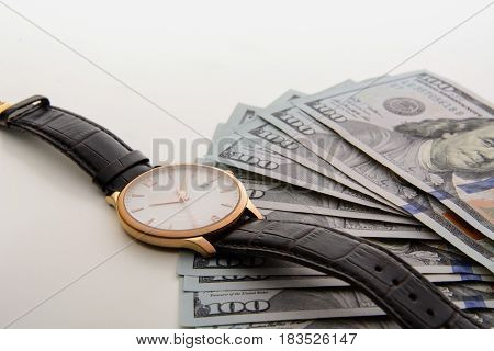 Time is money. Watch and dollars on the grey background