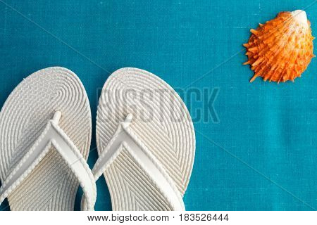 White Flip Flop Near Seashell On Blue Background. Top View.
