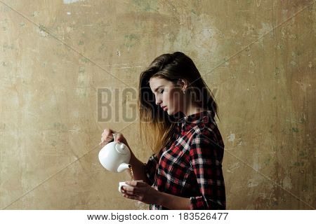 service and serving pretty woman with stylish blond long hair in red plaid shirt and blue jeans holding white ceramic tea pot teapot on beige wall. Teatime and ceremony