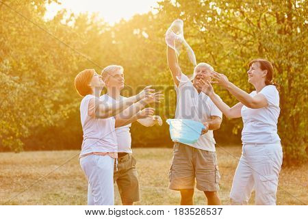 Group of senior citizens making soap bubbles and having fun in the park