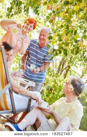Happy seniors in the garden in summer drinking coffee