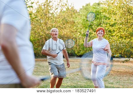 Active seniors playing badminton in the park in summer