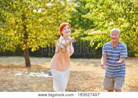Senior couple playing frisbee and having fun in summer in the park