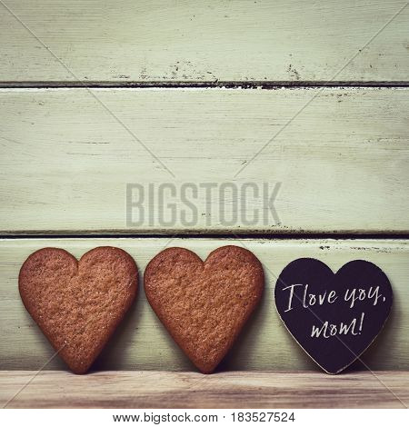 closeup of a pair of heart-shaped cookies and a heart-shaped black signboard with the text I love you mom written in it, against a pale green rustic wooden background