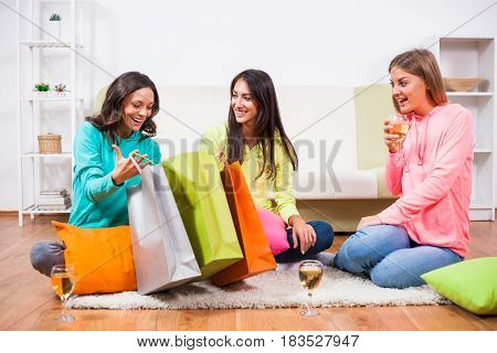 Three friends are sitting in room with shopping bags and talking.